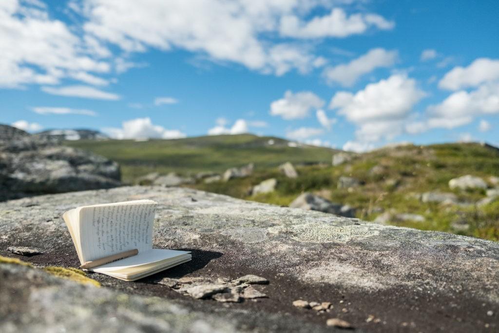 En skrivbok med text på en sten i fjällen